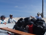 The crew about to leave East Island after a day of hand-pulling sandbur, an invasive annual grass we are working to eradicate from the island. All those garbage bags are full of sandbur! (Photo by Megan Juran)